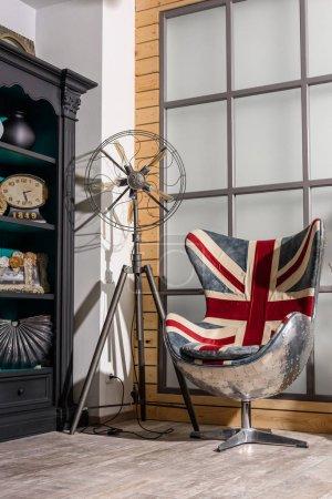 Photo pour Intérieur de style rétro moderne salon avec fauteuil avec grand drapeau britannique - image libre de droit