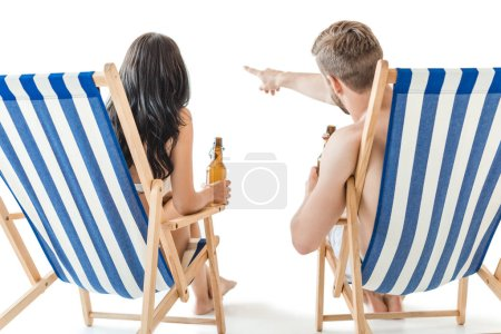 back view of couple with bottles of beer relaxing on beach chairs, isolated on white