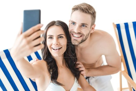 beautiful smiling couple taking selfie with smartphone on beach chairs, isolated on white