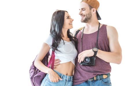 couple of smiling tourists with camera and backpacks hugging and looking at each other, isolated on white