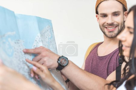 smiling couple of tourists pointing at map, isolated on white