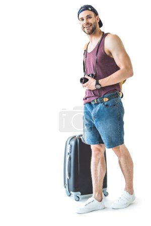 happy male tourist with travel bag and camera ready for trip, isolated on white
