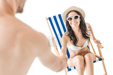 beautiful cheerful woman in swimsuit and sunglasses taking hands of her boyfriend, isolated on white