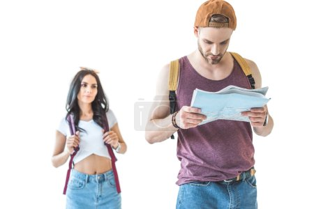 couple of tourists with backpacks looking at map, isolated on white