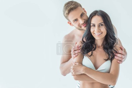 handsome man hugging his smiling girlfriend in swimwear, isolated on white