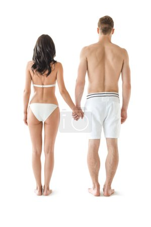 back view of young couple in swimwear holding hands, isolated on white