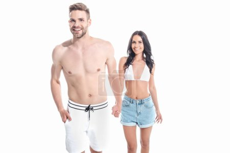 beautiful smiling couple in swimwear holding hands, isolated on white
