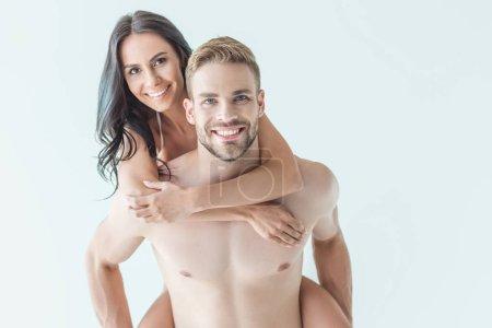 bel homme souriant, sa petite amie le ferroutage et regardant la caméra, isolé sur blanc