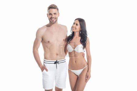 young couple in swimwear embracing isolated on white