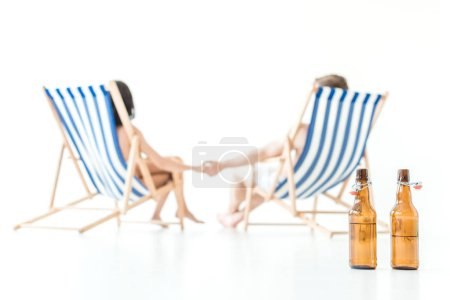 selective focus of couple holding hands and resting on beach chairs, with bottles of beer on foreground, isolated on white