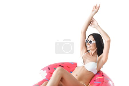 young woman in sunglasses relaxing on inflatable donut, isolated on white