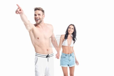 excited couple holding hands and pointing somewhere, isolated on white