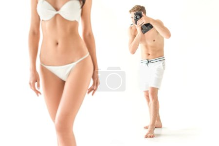 Photo for Photographer taking photo of beautiful slim woman in swimwear, isolated on white - Royalty Free Image