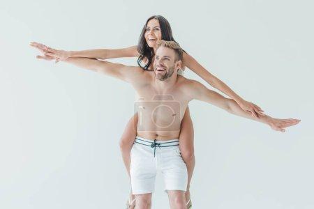 cheerful man piggybacking his beautiful girlfriend, isolated on white