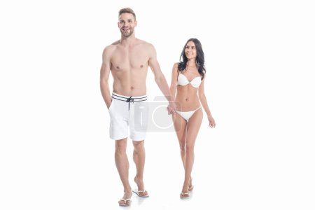 Photo for Beautiful couple in swimwear holding hands, isolated on white - Royalty Free Image