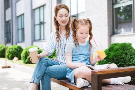 smiling kid with juice reading book with mother near by while resting on bench together on street