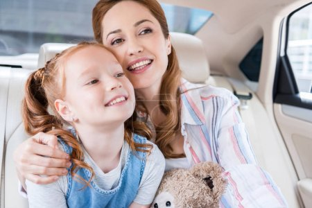 portrait of happy mother and daughter with teddy bear sitting in car