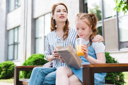 Photo for Kid drinking juice and reading book with mother near by while resting on bench together on street - Royalty Free Image