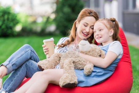 Foto de Madre sonriente con café para llevar y su hija con osito descansando juntos en la silla del bolso de haba - Imagen libre de derechos