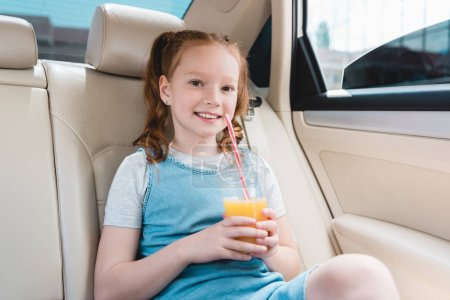 portrait of cheerful kid with juice sitting in car