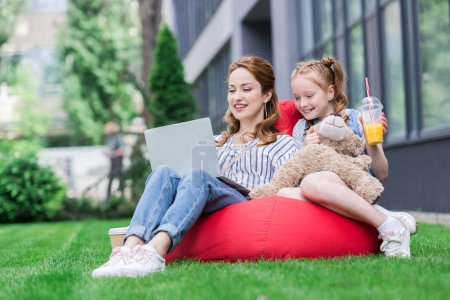 mother and daughter using laptop while resting on bag chair together