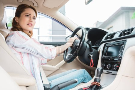 side view of emotional woman honking horn while driving car