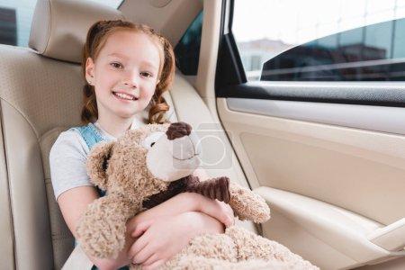 portrait of cheerful kid hugging teddy bear while sitting in car