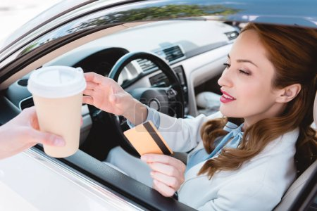 businesswoman with credit card in hand taking coffee to go while sitting in car