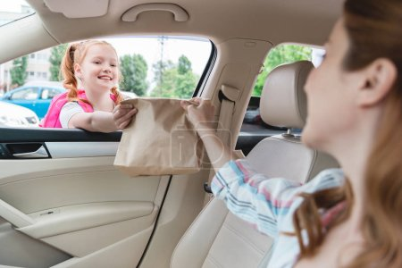 partial view of woman in car giving paper package with food to daughter