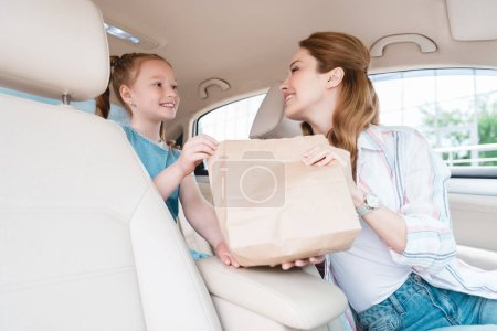 smiling woman giving paper package with food to daughter in car