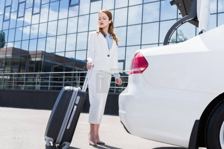 side view of businesswoman in white suit with suitcase standing at car on street
