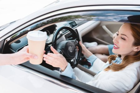 smiling businesswoman in car taking coffee to go from shop assistant