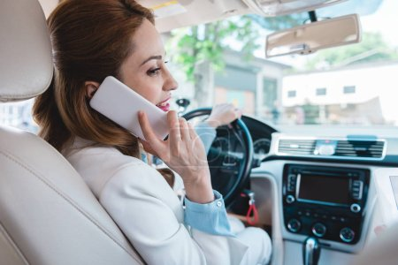 side view of smiling businesswoman talking on smartphone while driving car
