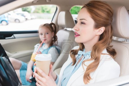 selective focus of businesswoman with coffee to go and daughter with juice near by in car