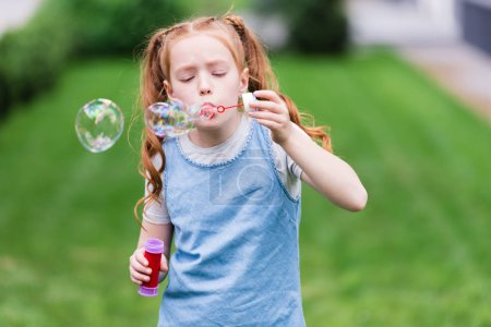portrait of cute child blowing soap bubbles in park