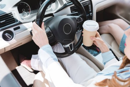 partial view of businesswoman with coffee to go driving car with daughter near by