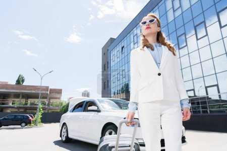 low angle view of businesswoman in white suit and sunglasses with suitcase standing at car on street
