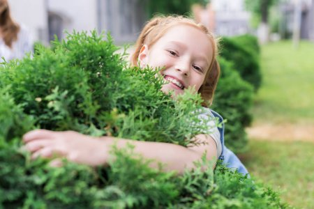 portrait of cheerful child hugging green bush