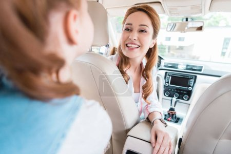 partial view of smiling mother looking at daughter on passengers seat
