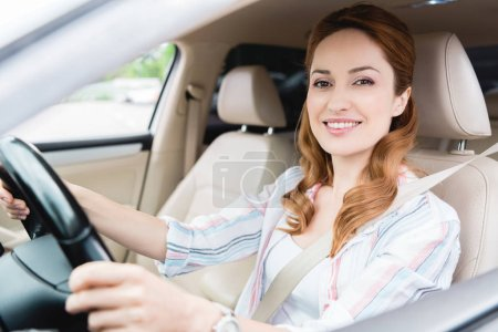 Photo for Side view of smiling woman looking at camera while driving car - Royalty Free Image