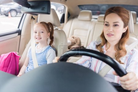 portrait of woman driving car with smiling daughter on passengers seat
