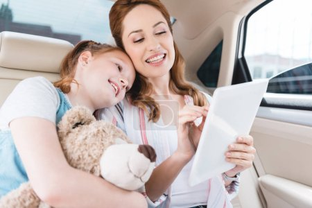 Photo for Portrait of smiling family using digital tablet together in car - Royalty Free Image