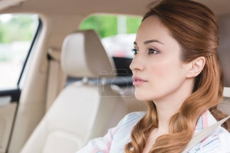 side view of focused woman driving car alone