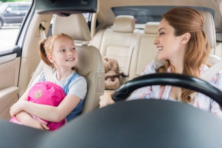 portrait of smiling mother driving car with daughter on passengers seat
