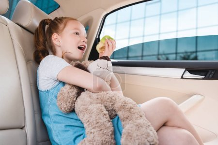 side view of emotional kid with teddy bear and fresh apple in car