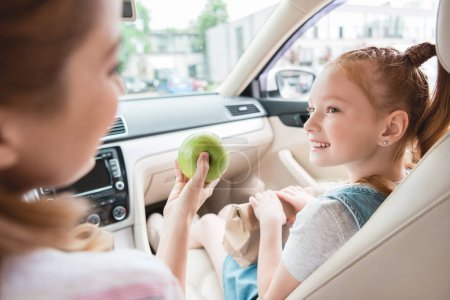 partial view of mother giving apple to smiling daughter in car