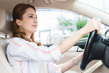 Photo for Side view of attractive woman driving car alone - Royalty Free Image