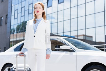 portrait of businesswoman in white suit with suitcase standing at car on street
