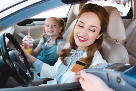 smiling businesswoman paying with credit card for take away order in car