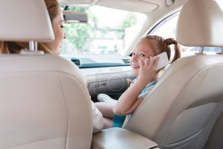 side view of smiling kid talking on smartphone with mother near by in car
